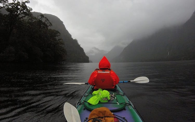 man in kayak on rainy day